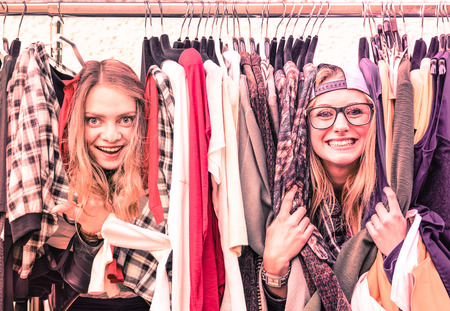 Foto de Young hipster women at clothes flea market  Best friends sharing fun time shopping in the city  Urban girlfriends enjoying happy life moments  Soft focus on vintage pink marsala filtered look - Imagen libre de derechos
