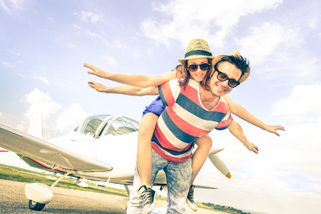 Photo pour Happy hipster couple in love on airplane travel honeymoon vacation  Summer concept with male and female models at exclusive trip excursion  Best friends having fun  Bright vintage filtered look - image libre de droit