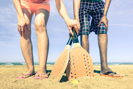 Best friends ready to play beach tennis game at beginning of summer - Concept of multiracial friendship and love - Fun and sport against racism - Vintage filtered look with nostalgic color tones