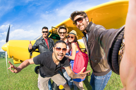 Foto de Best friends taking selfie at aeroclub with ultra light airplane  - Imagen libre de derechos