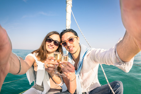 Foto de Young couple in love taking selfie on sailing boat cheering with champagne wine  Happy jubilee party cruise travel on luxury sailboat with boyfriend and girlfriend  Bright sunny afternoon color tone - Imagen libre de derechos