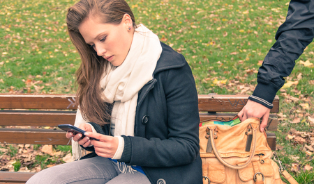 Foto de Pickpocketing from the bag of a young woman in a park - Imagen libre de derechos