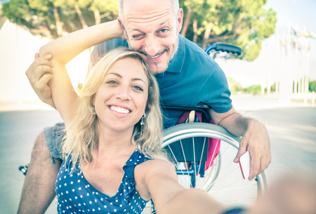 Foto de Happy couple in love taking selfie in urban city background - Disability positive concept with man on wheelchair - Vintage retro filtered look with soft focus on smiling woman due to sun flare halo - Imagen libre de derechos