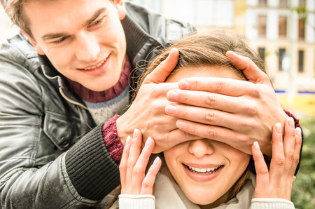 Photo for Young man covering the eyes of an happy surprised girlfriend - Royalty Free Image