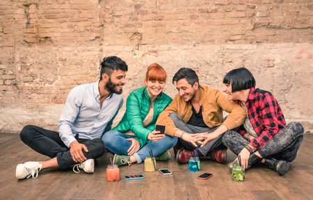 Foto de Group of hipster best friends with smartphones in grungy alternative location - Young entrepreneurs people resting at cocktail bar renovation - Friendship fun concept with trend technology interaction - Imagen libre de derechos