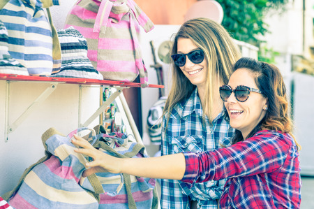 Photo for Young beautiful women girlfriends at flea market looking for bags - Best friends sharing free time having fun and shopping during travel - Soft vintage marsala filtered look - Focus on smallest girl - Royalty Free Image