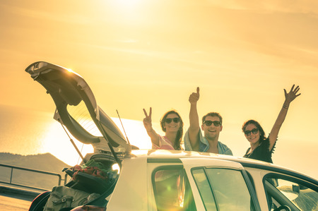Photo pour Best friends cheering by car road trip at sunset - Group of happy people outdoor on vacation tour - Friendship concept at travel with positive nostalgic emotions - Soft focus due to backlight contrast - image libre de droit