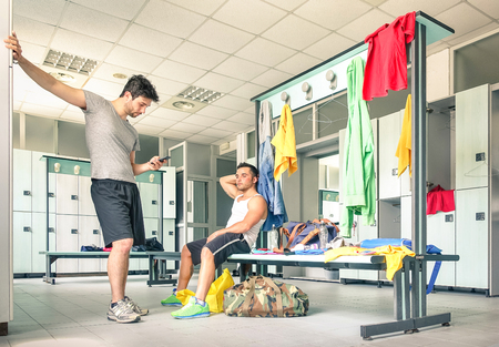 Foto per Young people at gym dressing room - Handsome guys at fitness studio doing their own staff before training - Social concept with lack of communication - Man looking at smartphone not talking to friend - Immagine Royalty Free