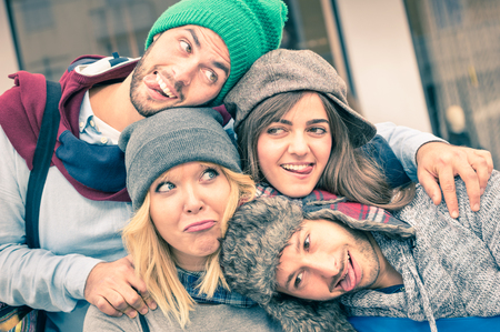Photo for Group of best friends taking selfie outdoors with funny face expression and fashion clothes - Happy friendship concept with young hipster people having fun together - Vintage desaturated filtered look - Royalty Free Image