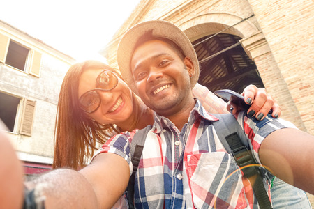 Foto de Multiracial couple taking selfie at old town trip - Fun concept with alternative fashion travelers - Indian boyfriend with caucasian girlfriend - Warm filter with powered sunlight and lens flare halo - Imagen libre de derechos