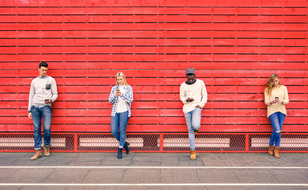Foto de Group of multiracial fashion friends using smartphone with red wood background - Technology addiction in urban lifestyle with disinterest towards each other - Addicted people to modern mobile phones - Imagen libre de derechos