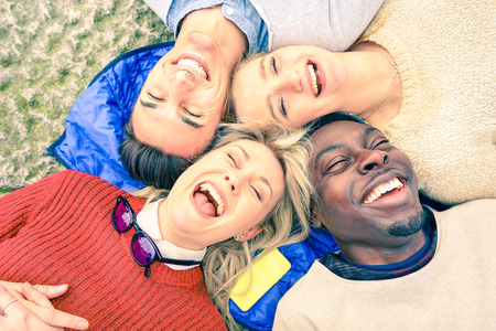 Photo for Multiracial best friends having fun and laughing together outdoor at springtime - Happy friendship concept with young people on fashion clothes - Upside down point of view - Soft vintage filtered look - Royalty Free Image