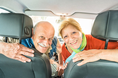 Photo pour Happy senior couple ready for driving car on journey trip - Concept of joyful active elderly with retired man and woman enjoying their best years - Modern mature travel lifestyle during retirement - image libre de droit
