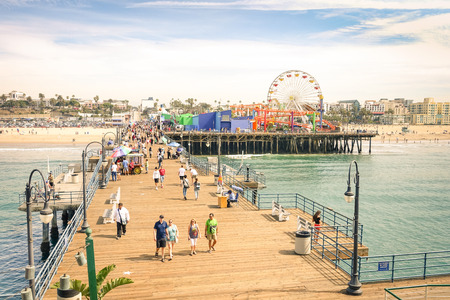 Photo for LOS ANGELES - 18 MARCH 2015: high angle view of international tourists and local people at Santa Monica Pier with ferris wheel of Pacific Amusement Park - Famous american landmark on californian coast - Royalty Free Image