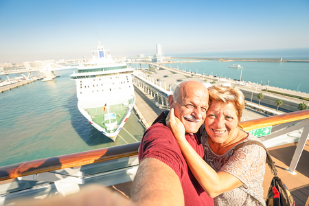 Foto de Senior happy couple taking selfie on ship at Barcelona harbour background - Mediterranean cruise travel tour - Active elderly concept with retired people around the world - Warm afternoon color tones - Imagen libre de derechos
