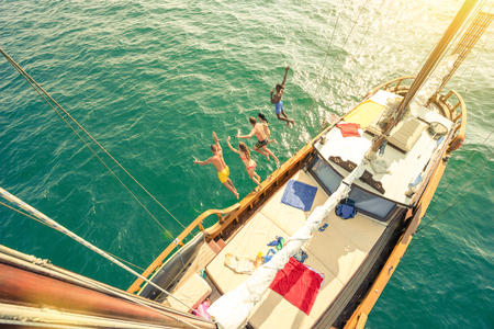 Photo pour Aerial view of young people jumping from sailing boat on sea trip - Rich happy friends having fun in summer party day - Exclusive vacation concept - Warm vintage filter with enhanced sun flare halos - image libre de droit