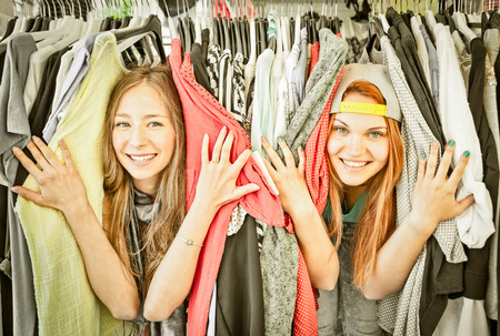 Foto de Young beautiful women at flea market - Girls best friends sharing free time having fun and shopping together - Girlfriends enjoying everyday life moments - Vintage filtered look with soft vignetting - Imagen libre de derechos