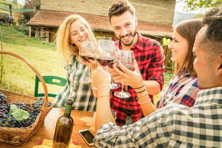 Photo pour Happy friends having fun and drinking wine - Friendship concept with young people enjoying harvest time together at farmhouse vineyard countryside - Warm filter with focus on faces in center of frame - image libre de droit