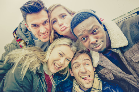 Photo for Best friends taking selfie outdoor on autumn winter clothes - Happy youth concept with multiracial people having fun together - Royalty Free Image