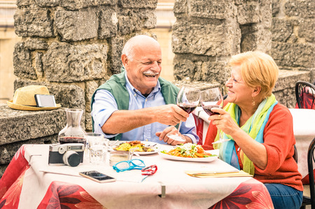 Photo pour Senior couple having fun and eating at restaurant during travel - Mature man and woman wife in old city town bar during active elderly vacation - Happy retirement concept with retired people together - image libre de droit