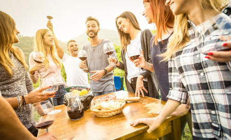 Photo pour Young friends having fun outdoor drinking red wine - Happy people enjoying harvest time at farmhouse vineyard winery - Youth friendship concept with focus on guy toasting in middle frame - Warm filter - image libre de droit