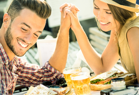 Photo pour Couple in love taking selfie at beer bar on travel excursion - Young happy tourists enjoyng happiness moment at street food restaurant - Relationship concept with soft focus and desat contrast filter - image libre de droit