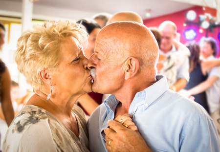 Photo for Happy senior retired couple having fun on dancing at restaurant wedding celebration party - Love concept of joyful elderly and retirement lifestyle with man lovely kissing wife - High iso color image - Royalty Free Image