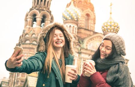 Foto de Happy girlfriends taking winter selfie at  Savior on Spilled Blood  church in Saint Petersburg - Friendship concept with girls having fun together drinking coffee outdoor - Focus on left young woman - Imagen libre de derechos