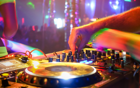 Photo for Close up of dj playing party music on modern cd usb player in disco club - Nightlife and entertainment concept  - Defocused background with shallow depth of field and focus on buttons near mixing hand - Royalty Free Image