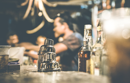 Photo for Blurred defocused side view of barman and people drinking and having fun at cocktail bar - Social gathering concept with people enjoying time together - Warm retro contrast filter with focus on shaker - Royalty Free Image
