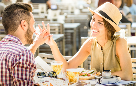 Photo pour Couple in love having fun at beer bar on travel excursion - Young happy tourists enjoying happy moment at street food restaurant - Relationship concept with focus on girl face on warm bright filter - image libre de droit