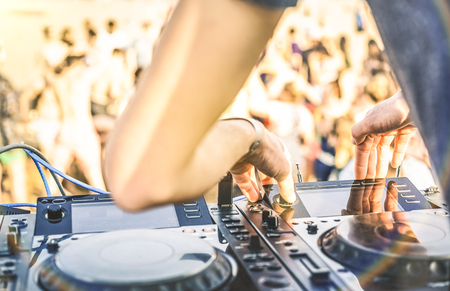 Photo for Close up of dj playing electro sound on modern cd usb player at summer beach party - Music festival and entertainment concept  - Defocused background with shallow depth of field - Focus on mixing hand - Royalty Free Image