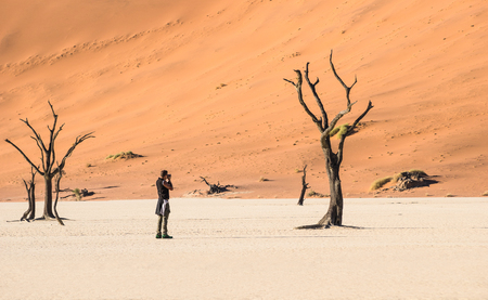 Photo for Lonely adventure travel photographer at Deadvlei crater in Sossusvlei territory - Namibian world famous desert - Wander concept with african nature wonder with unique wild landscape in Namibia - Royalty Free Image