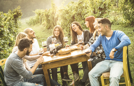 Foto de Happy friends having fun outdoor drinking red wine - Young people eating food at harvest time in farmhouse vineyard winery - Youth friendship concept with shallow depth of field - Warm contrast filter - Imagen libre de derechos