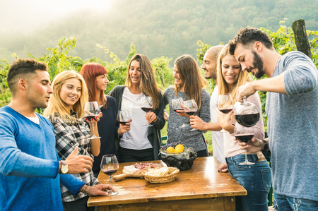 Photo pour Group of happy friends having fun outdoors drinking red wine - Young people eating local fresh food at grape harvesting in farmhouse vineyard winery - Youth friendship concept on a vivid warm filter - image libre de droit