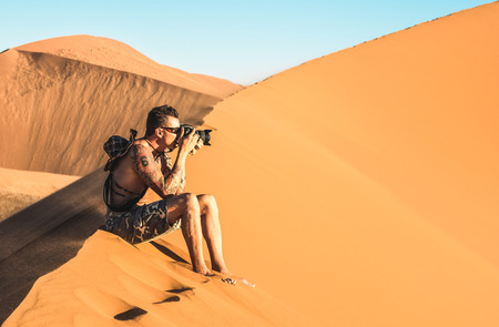 Photo for Lonely man photographer sitting on sand at Dune 45 in Sossusvlei - Concept of wanderlust in namibian famous desert - Adventure trip travel to african wonders in Namibia - Soft teal and orange filter - Royalty Free Image