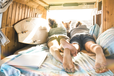 Foto de Hipster couple with cute dog traveling together on vintage van transport - Life inspiration concept with hippie people on minivan adventure trip watching sunset in relax moment - Warm sunshine filter - Imagen libre de derechos