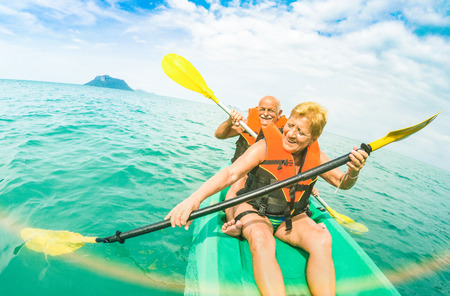 Foto de Senior happy couple taking travel selfie on kayak at Ang Thong marine park in Ko Samui - Trip to Thailand wonders - Active elderly concept around world - Tilted composition and sunshine flare filter - Imagen libre de derechos
