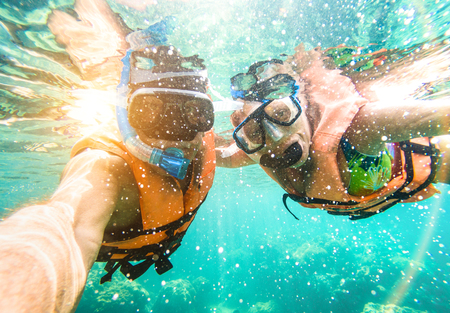 Foto de Senior happy couple taking selfie in tropical sea excursion with water camera - Boat trip snorkeling in exotic scenarios - Active retired elderly and fun concept on scuba diving - Warm vivid filter - Imagen libre de derechos