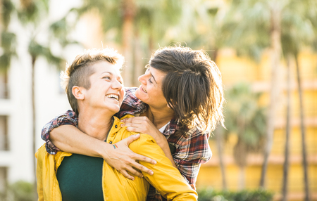 Photo pour Happy playful girlfriends in love sharing time together at travel trip on piggyback hug - Women friendship concept with girls couple having fun on fashion clothes outdoors - Bright warm sunset filter - image libre de droit