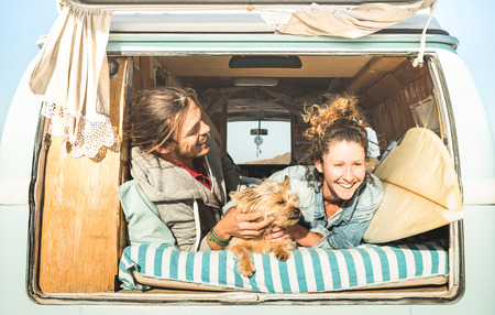 Photo pour Hipster couple with cute dog traveling together on vintage mini van transport - Life inspiration concept with hippie people on minivan adventure trip in relax moment - Bright warm retro filter - image libre de droit