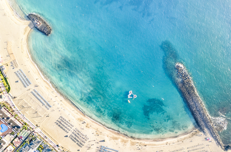 Foto de Aerial view of Los Cristianos bay beach in Tenerife with sunbeds and umbrellas miniature - Travel concept with nature wonder landscape in Canary islands Spain - Bright warm day filter - Imagen libre de derechos