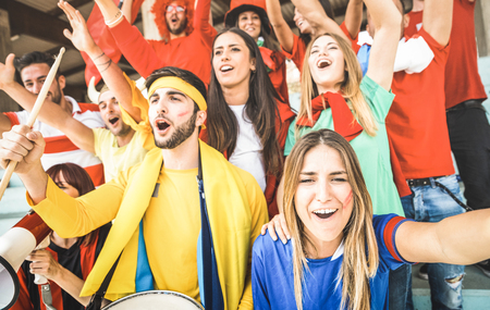 Foto de Young football supporter friends cheering and watching soccer cup match at intenational stadium - People fans group with multicolored t-shirts having excited fun on sport world championship concept - Imagen libre de derechos