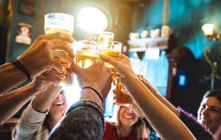 Foto de Group of happy friends drinking and toasting beer at brewery bar restaurant - Friendship concept with young people having fun together at cool vintage pub - Focus on middle pint glass - High iso image - Imagen libre de derechos
