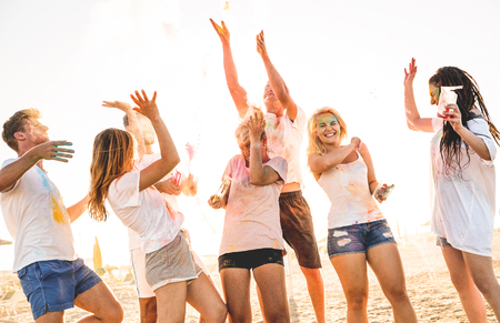 Foto de Group of happy friends having fun at beach party on holi colors summer festival - Young people laughing together with genuine carefree mood - Youth and friendship concept with multi colored powder - Imagen libre de derechos