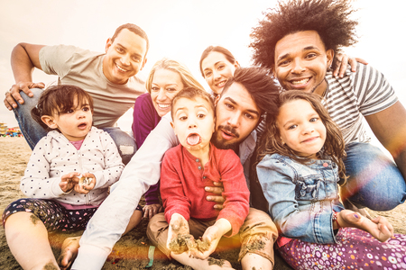 Foto de Happy multiracial families taking selfie at beach making funny faces - Multicultural happiness joy and love concept with mixed race people having fun outdoor at sunset - Bright pastel backlight filter - Imagen libre de derechos