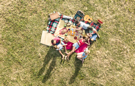 Photo pour Aerial drone view of happy families having fun with kids at picnic barbecue party - Multiracial happiness and love concept with mixed race people playing with children at park - Warm bright filter - image libre de droit