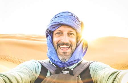 Foto de Young man solo traveler taking selfie at Erg Chebbi desert dune near Merzouga in Morocco - Adventure wanderlust concept on world famous nature wonder in Maroc - Warm bright sunset color filtered tones - Imagen libre de derechos
