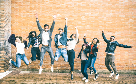 Foto de Happy friends millennials jumping and cheering against brick wall in the city - Friendship lifestyle and team concept with young people millenial having fun together - Teal and orange vintage filter - Imagen libre de derechos
