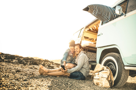Foto de Hipster couple traveling together on oldtimer mini van transport - Travel lifestyle concept with indie people on minivan adventure trip having fun with mobile smart phone - Warm desaturated filter - Imagen libre de derechos